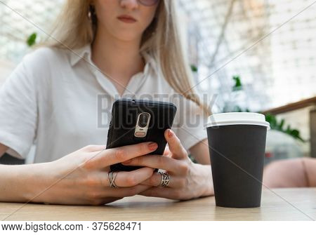 Cropped Photo Of Cheerful Young Caucasian Blond Business Woman In A White Shirt Typing On Smartphone