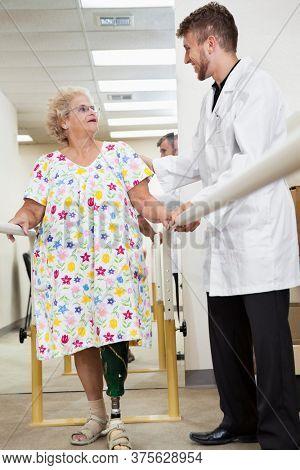 Young technician communicating with senior woman having ambulatory therapy