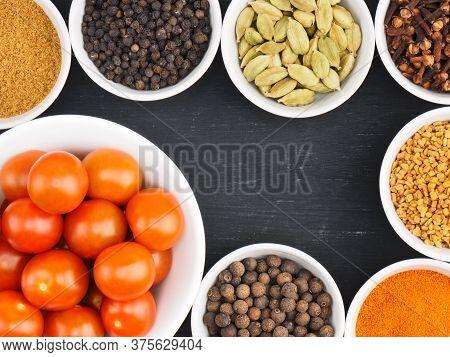 Red Small Cherry Tomato In White Bowl, Spice Cloves, Red Chili Pepper, Black Pepper, Masala Powder,