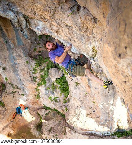 A Strong Man Climbs A Cliff, Climber Overcomes A Difficult Climbing Route On A Natural Terrain, Rock