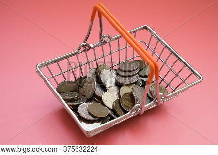 There Is A Handful Of Coins In The Shopping Basket. The Concept Of Buying Or Selling Currency. Purch