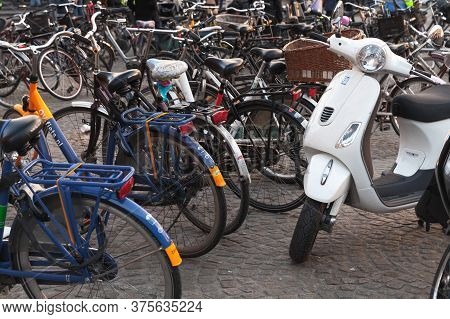 Amsterdam, Netherlands - February 24, 2017: White Vespa Scooter Stands Near Bicycles On A Parking Lo