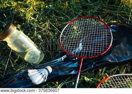 Bottle With Water And Lemons And Badminton Racquet In Green Grass Closeup