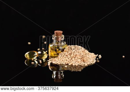 Sesame Oil In A Glass Bottle And Sesame Seeds On The Black Background.
