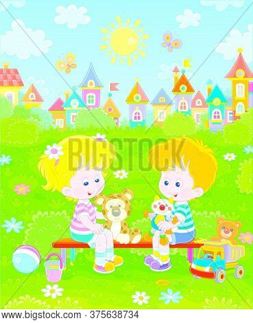 Cheerful Small Children Sitting On A Bench, Talking And Playing With Their Funny Colorful Toys On A