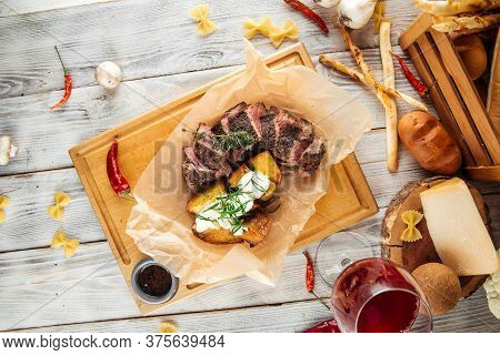 Top View On Sliced Lumbar Steak, Thin Sirloin With Baked Potatoes And Sour Cream, Horizontal