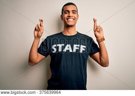 Young handsome african american worker man wearing staff uniform over white background gesturing finger crossed smiling with hope and eyes closed. Luck and superstitious concept.