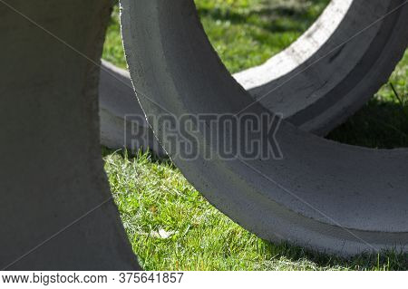 Massive Concrete Rings Lay On Green Grass, Abstract Industrial Photo Background