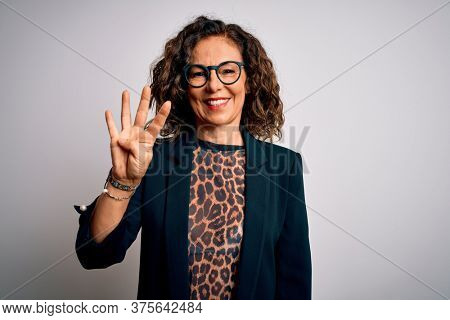 Middle age brunette business woman wearing glasses standing over isolated white background showing and pointing up with fingers number four while smiling confident and happy.