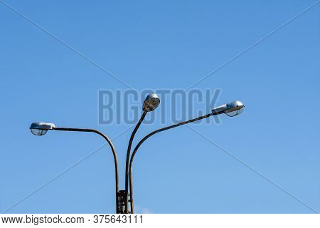 Street Lights On A Pole Against The Blue Sky -background Image