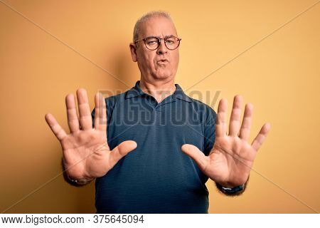 Middle age handsome hoary man wearing casual polo and glasses over yellow background doing stop gesture with hands palms, angry and frustration expression