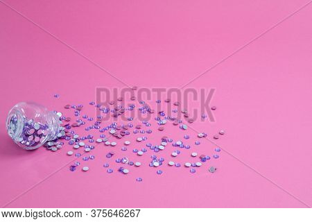 Lilac Spangles Are Scattered From A Bottle On A Pink Background