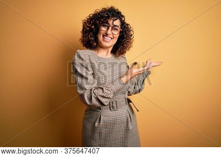 Beautiful arab business woman wearing dress and glasses standing over yellow background Inviting to enter smiling natural with open hand