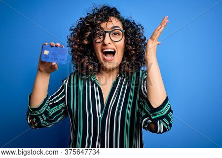 Young beautiful curly arab woman wearing glasses holding credit card money for payment very happy and excited, winner expression celebrating victory screaming with big smile and raised hands