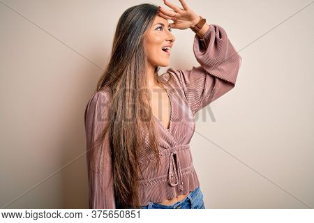 Young beautiful brunette elegant woman with long hair standing over isolated background very happy and smiling looking far away with hand over head. Searching concept.