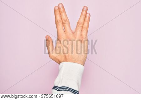 Hand of caucasian young man showing fingers over isolated pink background greeting doing Vulcan salute, showing back of the hand and fingers, freak culture