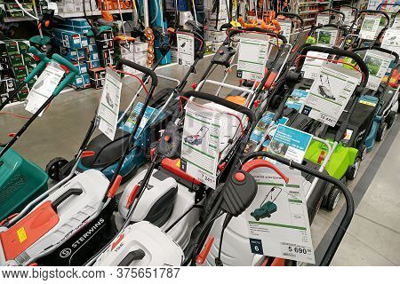 Moscow, Russia - August 17, 2019: Contemporary Petrol And Electric Lawn Mowers In A Building Materia