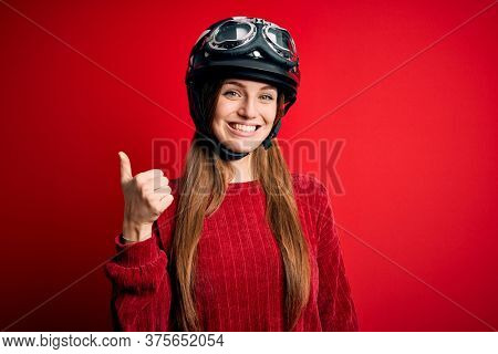 Young beautiful redhead motocyclist woman wearing moto helmet over red background doing happy thumbs up gesture with hand. Approving expression looking at the camera showing success.