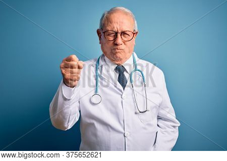 Senior grey haired doctor man wearing stethoscope and medical coat over blue background angry and mad raising fist frustrated and furious while shouting with anger. Rage and aggressive concept.
