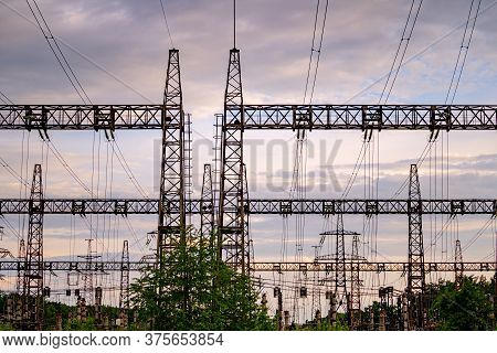 Energy Distribution Network. Electricity Pylons Against Orange And Yellow Sunset. Selective Focus.