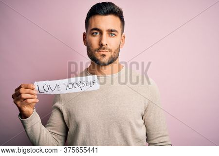 Young handsome man holding paper with self love message over pink background with a confident expression on smart face thinking serious