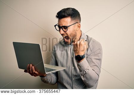 Young business man wearing glasses working using computer laptop annoyed and frustrated shouting with anger, crazy and yelling with raised hand, anger concept