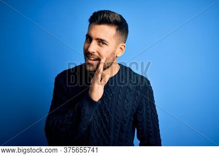 Young handsome man wearing casual sweater standing over isolated blue background hand on mouth telling secret rumor, whispering malicious talk conversation