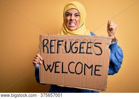 Beautiful arab woman wearing islamic hijab holding banner with refugees welcome message annoyed and frustrated shouting with anger, crazy and yelling with raised hand, anger concept
