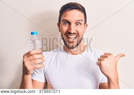 Young handsome man drinking bottle of water to refreshment over isolated white background pointing thumb up to the side smiling happy with open mouth