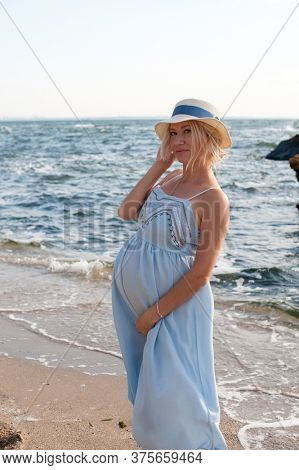 Happy future mother posing near ocean in blue provence style dress and hat, backlite
