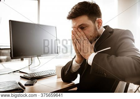 Business crisis concept. Emotional young businessman at work. Worried stressed manager sitting at the office table grabs his face with hands. Busy man in suit indoors shows negative emotions.