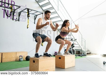 Fit Hispanic Young Man And Woman Doing Box Jump Exercise At Cross-training Gym
