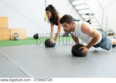 Dedicated Hispanic Young Couple Doing Push-ups On Medicine Balls At Fitness Club