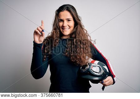 Beautiful motorcyclist woman with curly hair holding moto helmet over white background surprised with an idea or question pointing finger with happy face, number one