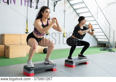 Determined Young Friends Doing Squats On Step Platforms During Cross-training At Fitness Studio