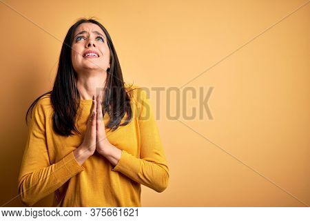 Young brunette woman with blue eyes wearing casual sweater over yellow background begging and praying with hands together with hope expression on face very emotional and worried. Begging.