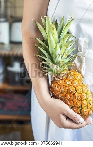 Cropped Young Woman In A White Cook Apron Holding A Ripe And Juicy Pineapple In Her Hands.