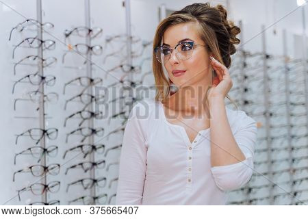 Happy Female Client Or Optician Is Standing With Set Of Glasses In Background In Optical Shop. Woman