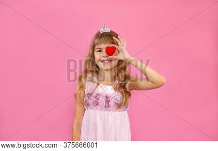 Little Girl On A Pink Background. Little Girl With A Heart In Her Hands. Little Girl Is Looking With