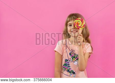 A Little Girl Is Looking Through A Lollipop. Little Girl On A Pink Background. Happy Child With Cand