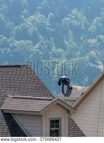 Young Roofing Contractor Replacing The Old Shingles On A Townhouse Roof High Above The Ground