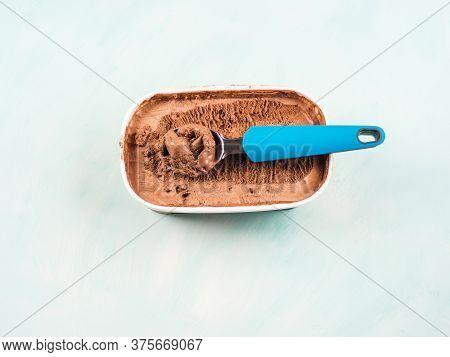 Ice Cream Scoop In Chocolate Ice Cream Tub On Green Turquoise Background. Closeup