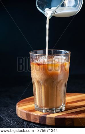 Milk Being Poured Into Iced Coffee In Tall Glass On Dark Background. Concept Refreshing Summer Drink