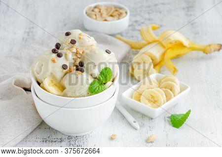 Homemade Vegan Banana Ice Cream In A Bowl With Peanuts And Chocolate On A Wooden Background. Healthy