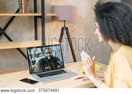 Back View Of Biracial Girl Talks Via Video Call With An African-american Male Colleague Or Friend On