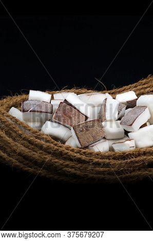 Coconut Pieces Place In Twisted Coir Ropes. On Isolated Black Background. Conceptual Photography,