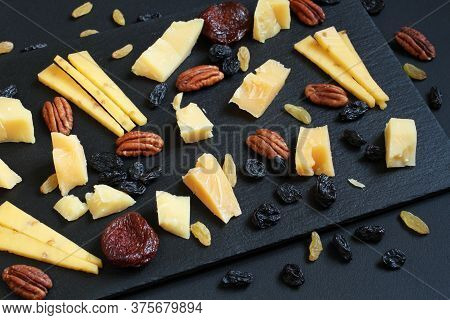 Pieces Of Parmesan Cheese And Gouda Cheese With Fenugreek, Blue And Gold Raisins And Dried Apricots