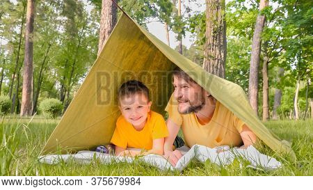 Father And Son In Tent. The Child Spends Time With His Father Outdoors. The Boy Laughs At Adult Joke