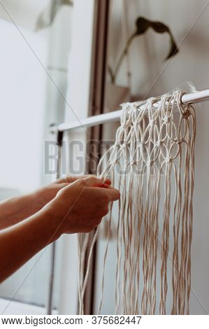 The Girl Weaves Macrame. Boho Decor In The Process Of Weaving. Hand Made