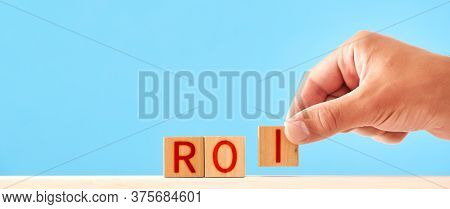 Roi Community Concept. Man Stacks Wooden Blocks In The Inscription Roi
